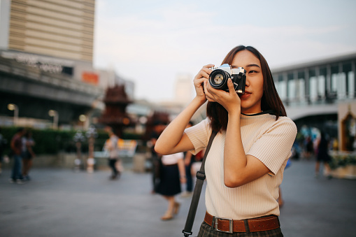 Young Asian woman traveler in Bangkok downtown district, holding a vintage film camera