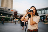Vintage colored portrait of a young Asian woman traveler, relaxing at the busy Siam station of the Skytrain, next to popular shopping malls and restaurants. She is wearing casual clothing, taking photos with her beautiful analog film camera with a fixed, large aperture, prime lens.