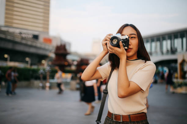 Young Asian woman traveler in Bangkok downtown district, holding a vintage film camera stock photo