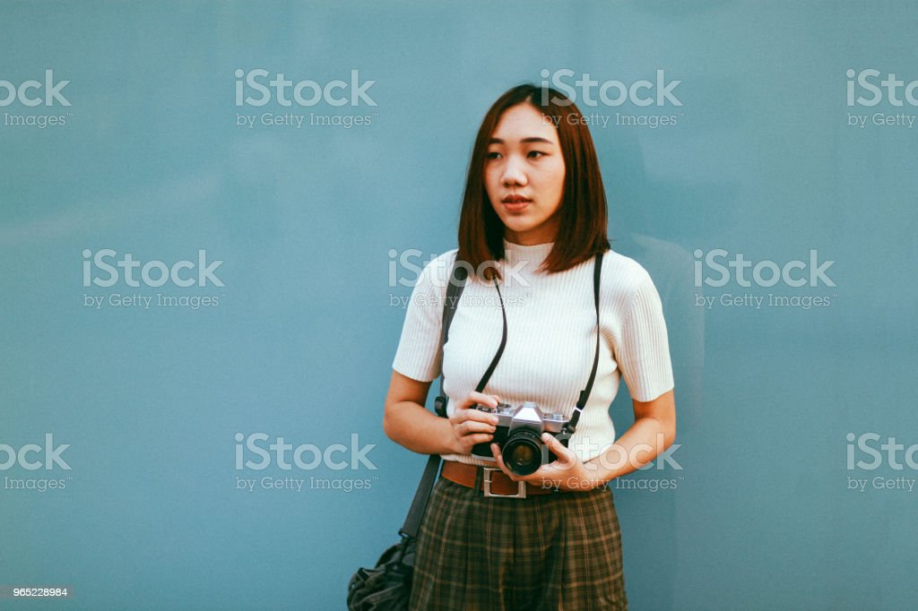 Young Asian woman traveler in Bangkok downtown district, holding a vintage film camera zbiór zdjęć royalty-free