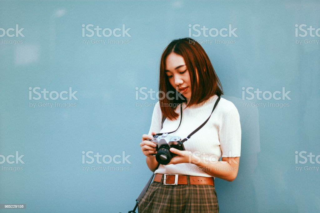 Young Asian woman traveler in Bangkok downtown district, holding a vintage film camera royalty-free stock photo