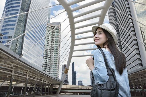Young asian woman traveler with a backpack on her shoulder walking on pathway bridge over modern city tower in Bangkok, Thailand, Travel holiday relaxation concept