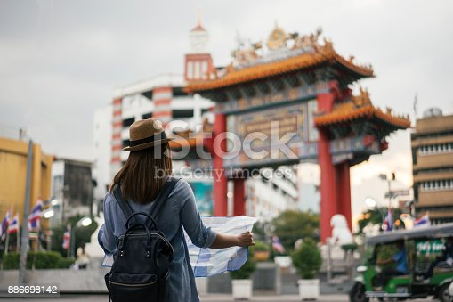 istock Young asian woman traveler with blue backpack and hipster hat looking map with tuk tuk Thailand background at China Town Bangkok. Traveling in Bangkok Thailand 886698142