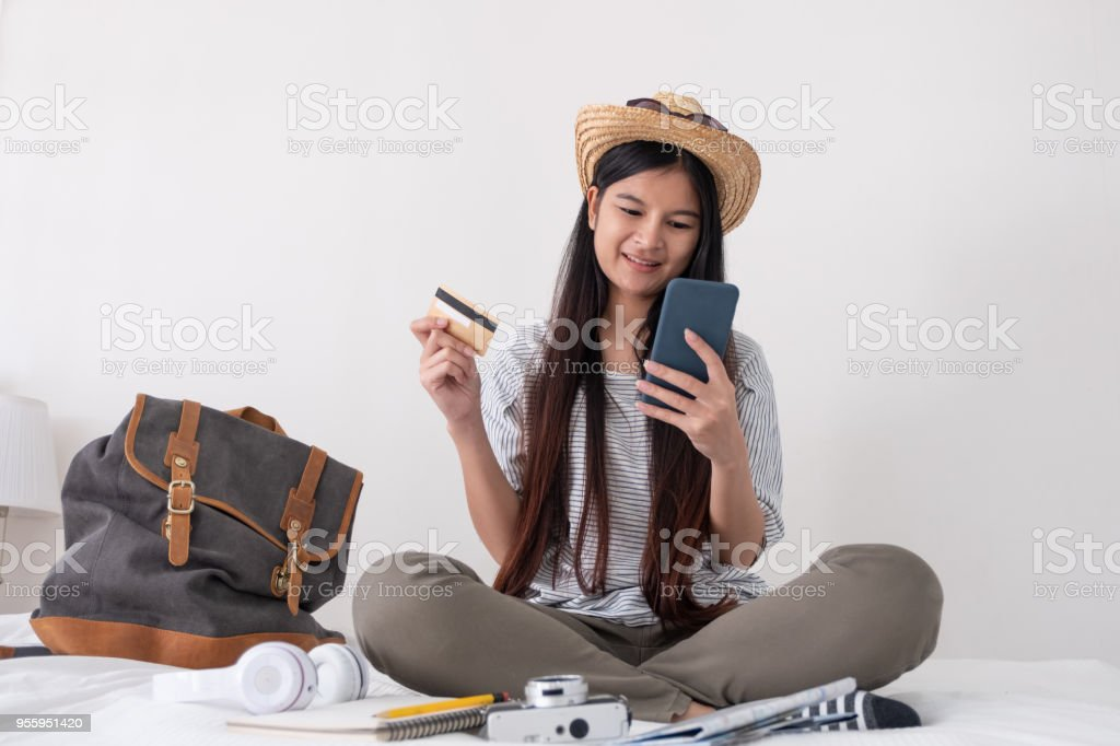 Young asian woman traveller planning vacation holiday expedition and booking ticket and hotel online with mobile phone app on bed.preparing to travel.digital lifestyle. stock photo