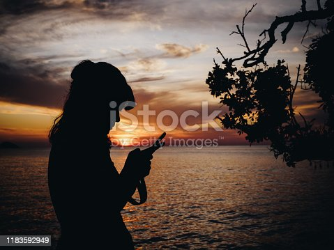 Young femal typing on smartphone by sea at sunset