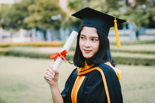 Young Asian woman university graduates celebrate with joyous and happiness with friends after receiving university degree certificate in commencement ceremony. Congratulations, graduation ceremony. Education concept. stock photo