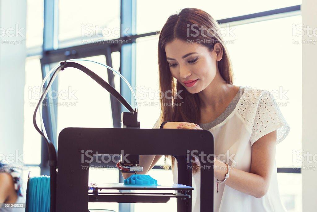 Young asian woman using 3D printer Start-up Business. Young asian woman using a 3D printer, watching at 3D printout. 2015 Stock Photo