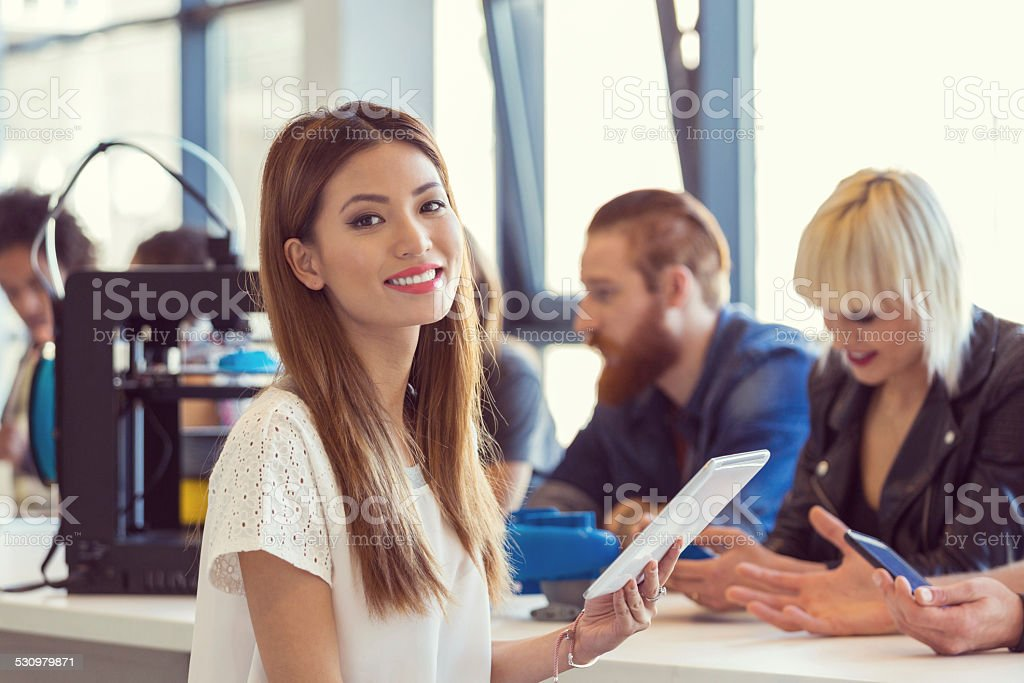 Young asian woman using digital tablet in 3D printer office Start-up Business. Focus on confident young asian man using a digital tablet and smiling at camera with group of people using 3D printer in the background. 2015 Stock Photo