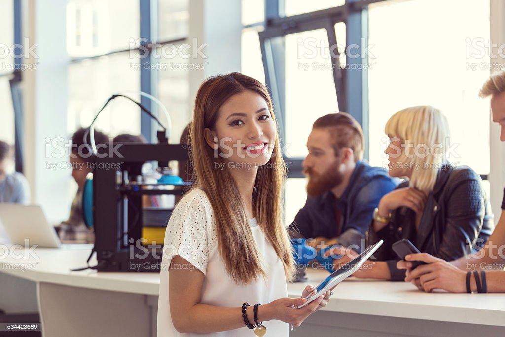 Young asian woman using digital tablet in 3D printer office Focus on young asian woman using a digital tablet with people working on 3D printers in the background.  2015 Stock Photo