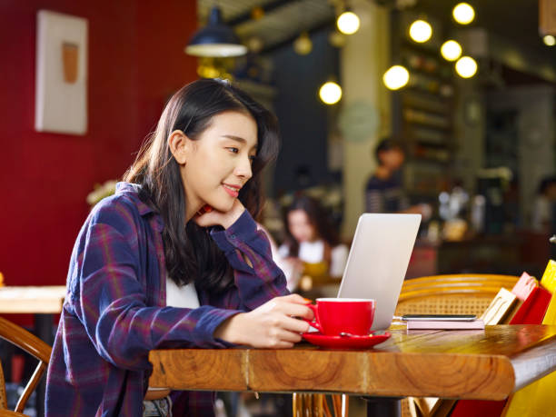 コーヒーを飲みながらノート パソコンを使用して若いアジア女性 - 大学生 パソコン 日本 ストックフォトと画像