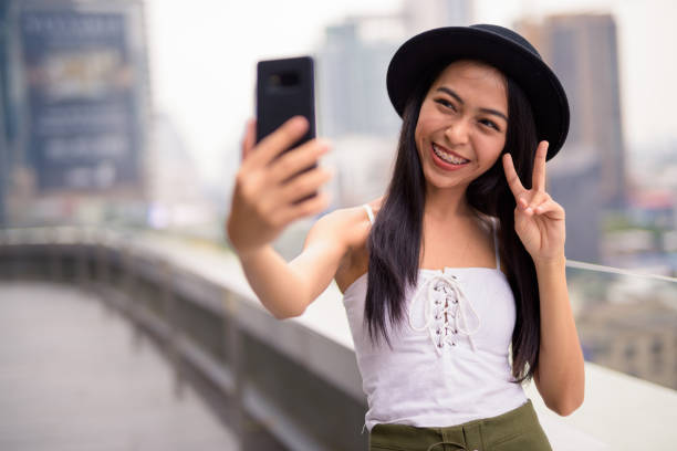 Young Asian Woman Using Mobile Phone Portrait Of Young Happy Asian Woman From Thailand Smiling suspenders stock pictures, royalty-free photos & images