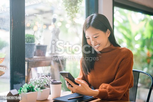 Young Asian woman using phone at a coffee shop happy and smile.