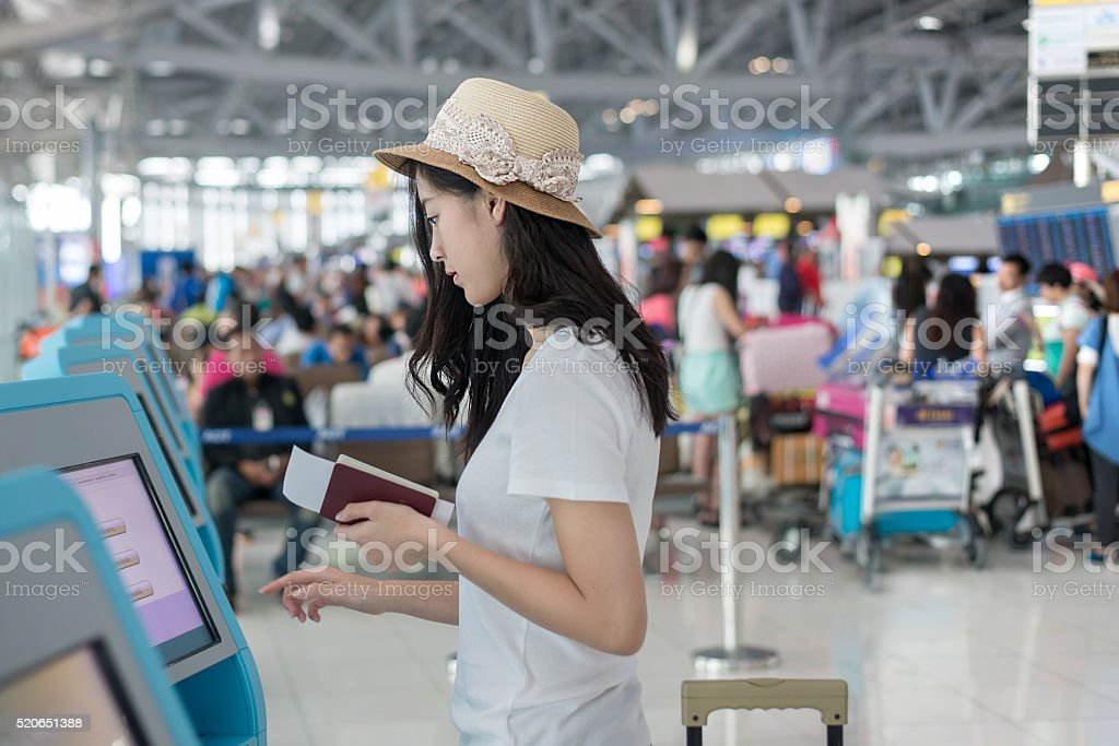 Young Asian woman using self check-in kiosks in airport stock photo