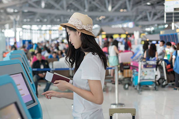 young asian woman using self check-in kiosks in airport - airport check in counter stock pictures, royalty-free photos & images