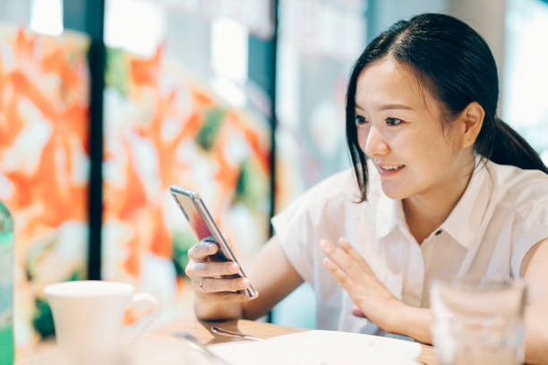ビジネス、オンラインショッピング、送金、金融、インターネットバンキングのためにスマートフォンを使用して若いアジアの女性。ぼやけた背景の上にコーヒーショップのカフェで。 - 利益 ストックフォトと画像
