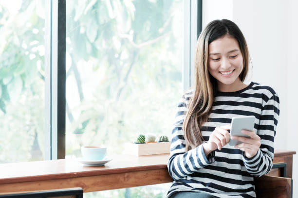 Young asian woman using smart phone while sitting by window cafe background, People technology and lifestyle stock photo