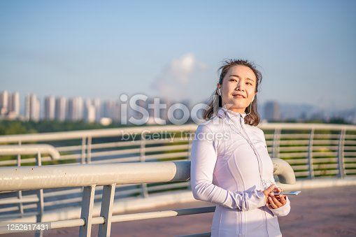 Young Asian woman using smartphone after exercising