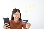 istock Young Asian woman using smartphone and credit card. Shopping buying online 1157571517