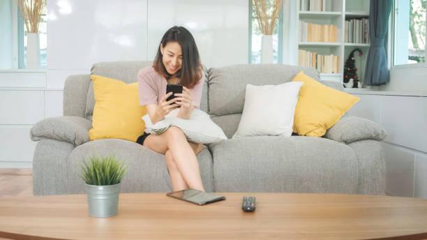 Junge asiatische Frau mit Smartphone Check Social Media Gefühl glücklich lächelnd, während auf dem Sofa liegen, wenn im Wohnzimmer zu Hause entspannen. Lifestyle Latin und hispanische ethnostizität Frauen im Haus Konzept. – Foto