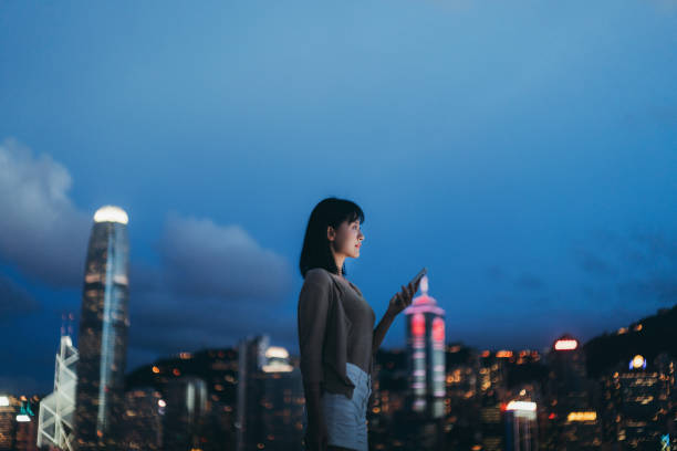 Young Asian woman using smartphone in the city, against illuminated city scene with highrise corporate skyscrapers at dusk