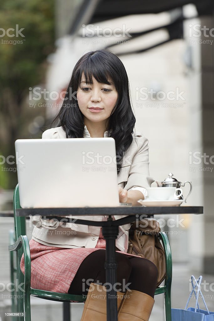 Young Asian Woman Using WiFi Laptop Computer in Internet Cafe royalty-free stock photo