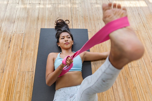 Shot of a beautiful young Asian woman lying down on the floor, using a pink yoga strap to practice flexibility at her home
