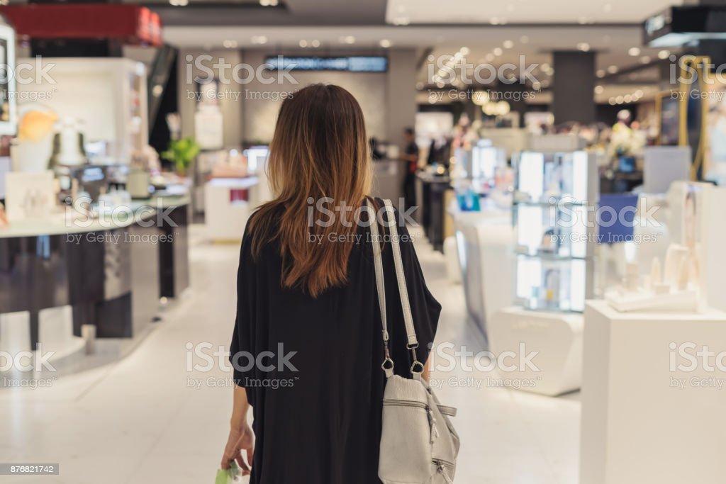 Junge asiatische Frau, die zu Fuß in Kosmetik-Abteilung in der mall – Foto