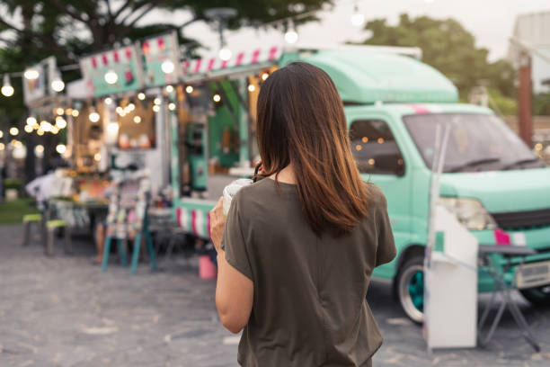 Young asian woman walking in the food truck market Young asian woman walking in the food truck market food truck stock pictures, royalty-free photos & images