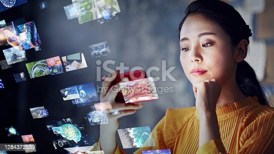 Young asian woman watching a lot of movies. Digital transformation.