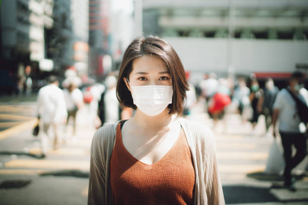 Young Asian woman wearing a protective face mask to prevent the spread of viruses in the city during the epidemic of Covid-19 health crisis