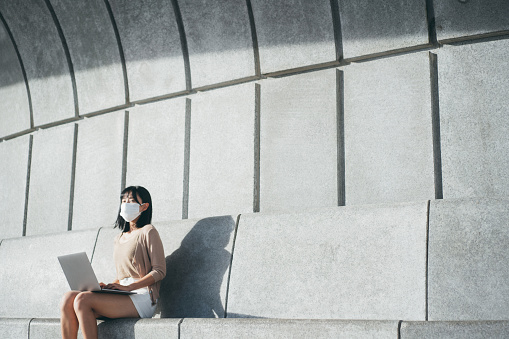 Young Asian woman wearing a protective face mask to protect and prevent from the spread of viruses in the city, working on a laptop outdoors in urban park against beautiful sunlight