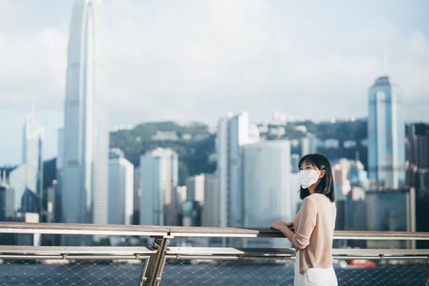Young Asian woman wearing a protective face mask to protect and prevent from the spread of viruses in the city, looking away while standing by the promenade of Victoria harbour against Hong Kong city skyline