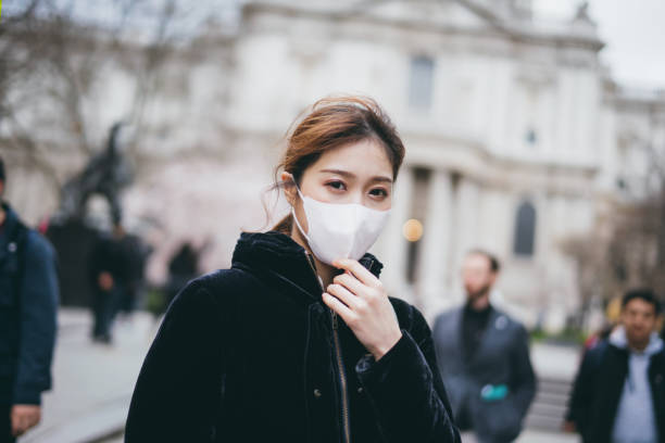 Young Asian woman wearing a surgical face mask to prevent the spread of viruses in the city