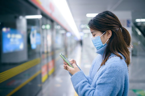 Young Asian woman wearing a surgical mask and waiting for subway train at subway station.