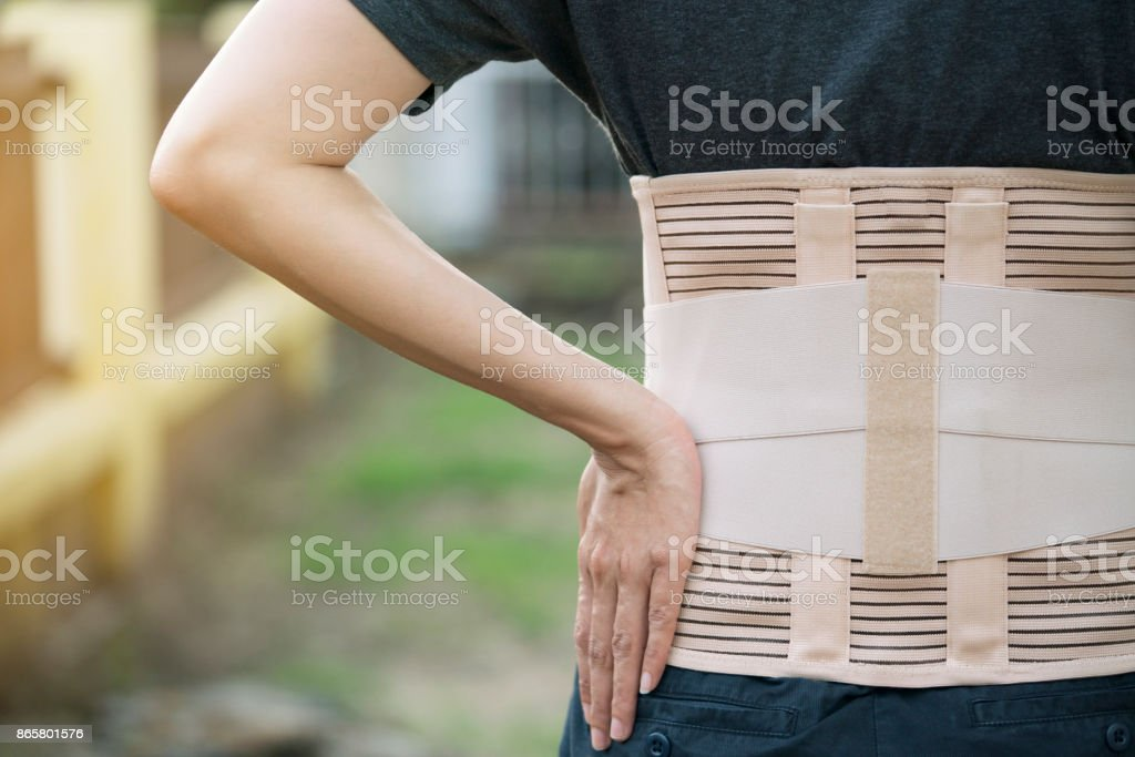 young asian woman wearing back support for protect her back, medicine and healthy concept stock photo