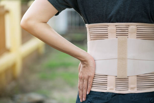 young asian woman wearing back support for protect her back, medicine and healthy concept young asian woman wearing back support for protect her back, medicine and healthy concept corset stock pictures, royalty-free photos & images