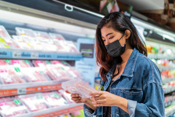 Young Asian woman wearing face mask in grocery store