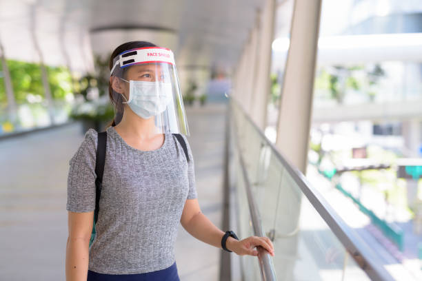 Young Asian woman wearing mask and face shield for protection from corona virus outbreak in the city stock photo
