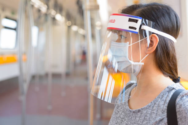 Young Asian woman wearing mask and face shield inside the train for protection from corona virus outbreak stock photo