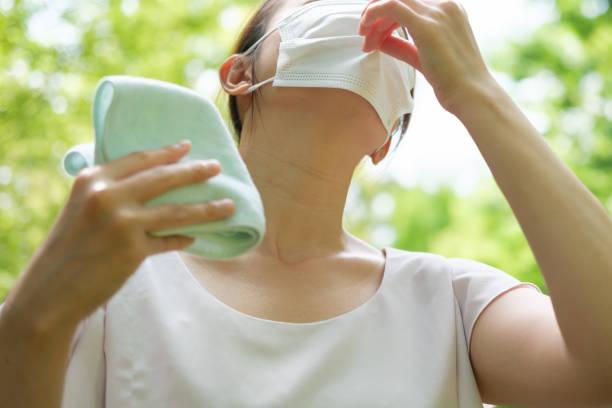 夏にマスクを着用した若いアジアの女性 - 熱さ ストックフォトと画像