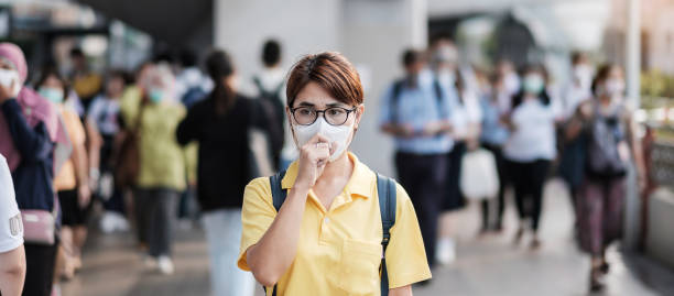 young asian woman wearing protection mask against novel coronavirus (2019-ncov) or wuhan coronavirus at public train station,is a contagious virus that causes respiratory infection.healthcare concept - sars foto e immagini stock