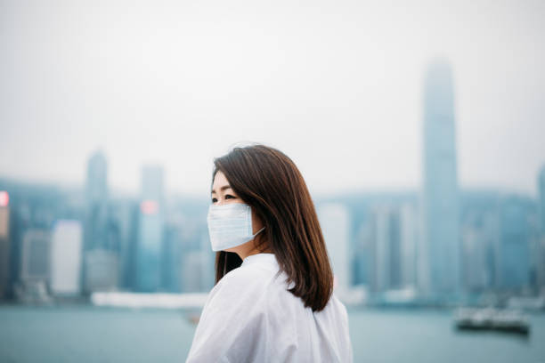 Young asian woman wearing protective face mask in city due to the polluted air or pm 2.5 and Coronavirus disease or COVID-19 outbreak situation in Hong Kong China and all of landmass in the world.
