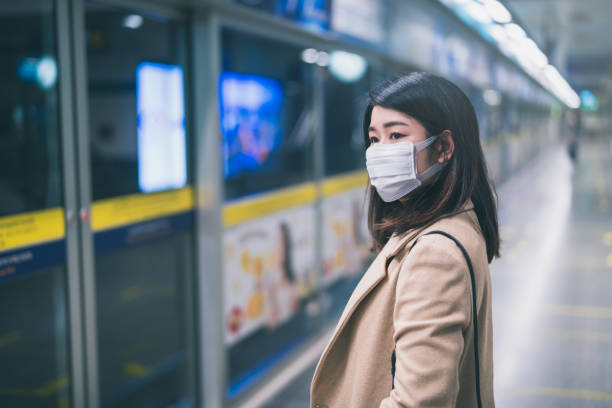 Young asian woman wearing protective face mask stand in line during waiting underground train in subway due to Coronavirus or COVID-19 outbreak situation in all of landmass in the world