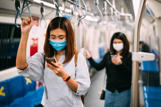 Young asian woman wearing protective face mask using smartphone in underground train due to the polluted air or pm 2.5 and Coronavirus or COVID-19 outbreak situation in all of landmass in the world.