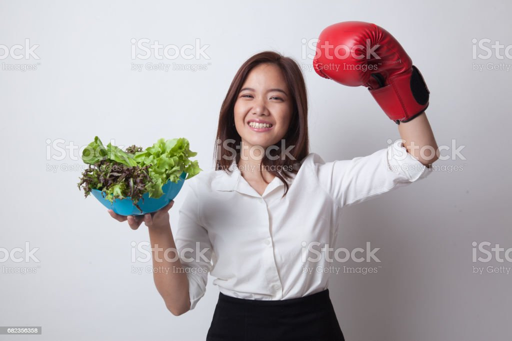 Young Asian woman with boxing glove and salad. foto stock royalty-free