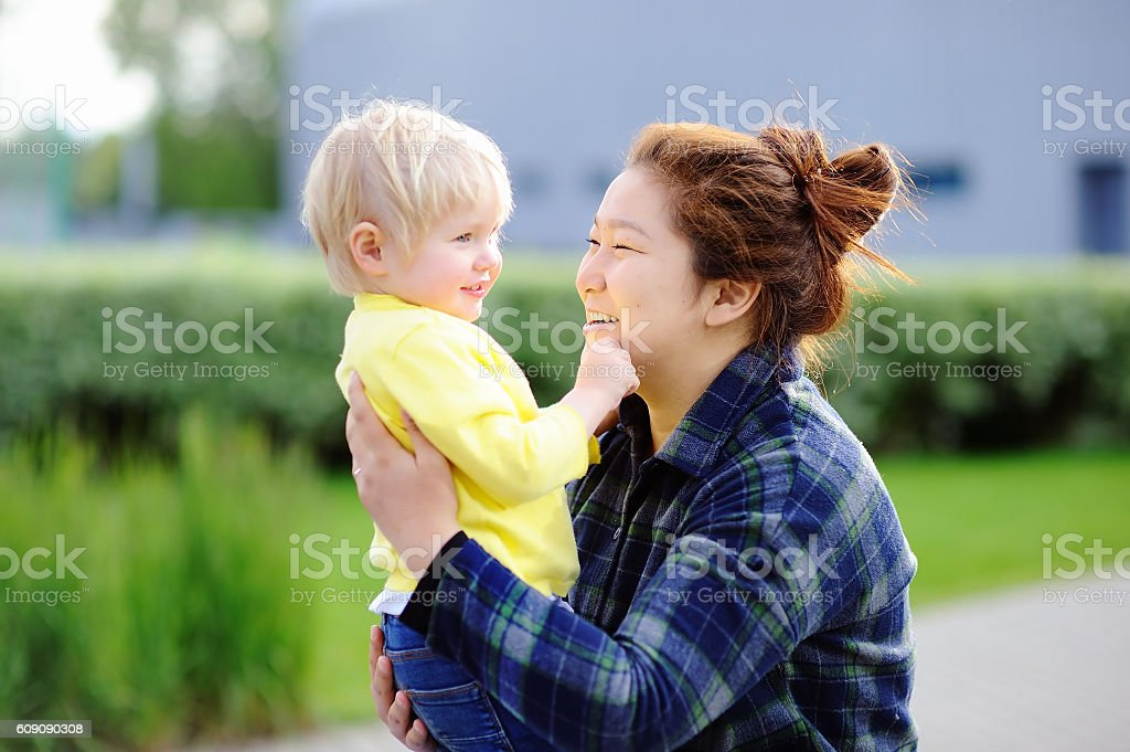 Young asian woman with cute caucasian toddler boy stock photo