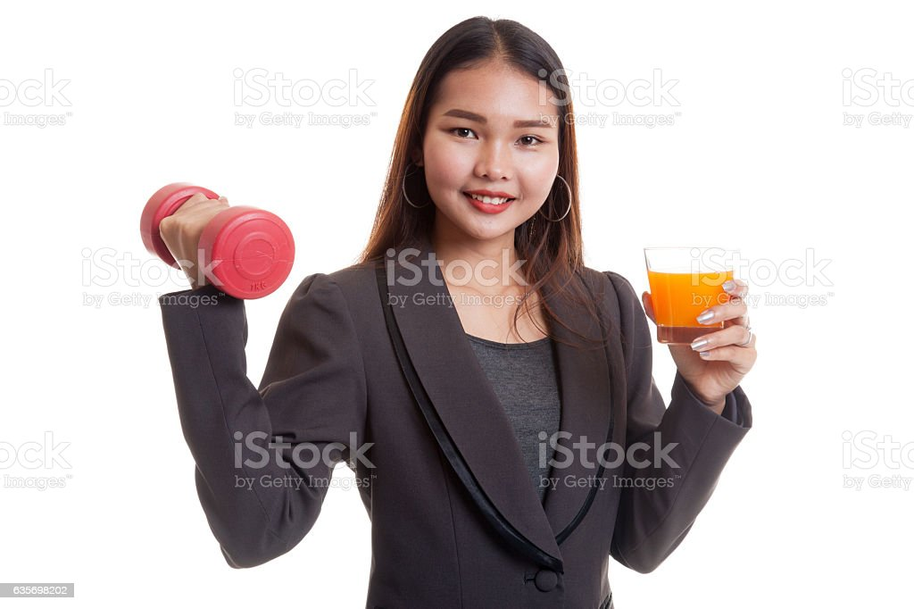 Young Asian woman with dumbbell drink orange juice. royalty-free stock photo