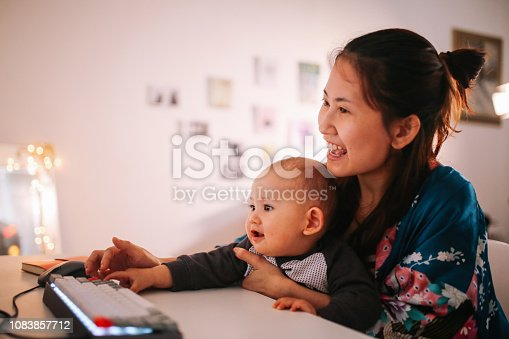 Portrait of a young Asian woman sitting with her baby boy at home, looking at the computer monitor. She might be using it to chat or video call her partner who is away, or just looking at some funny images. She is using a PC desktop computer with a modern but retro mechanical keyboard.