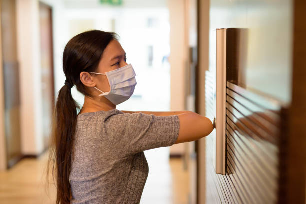 Young Asian woman with mask pressing elevator button with elbow for prevention of spreading the corona virus stock photo