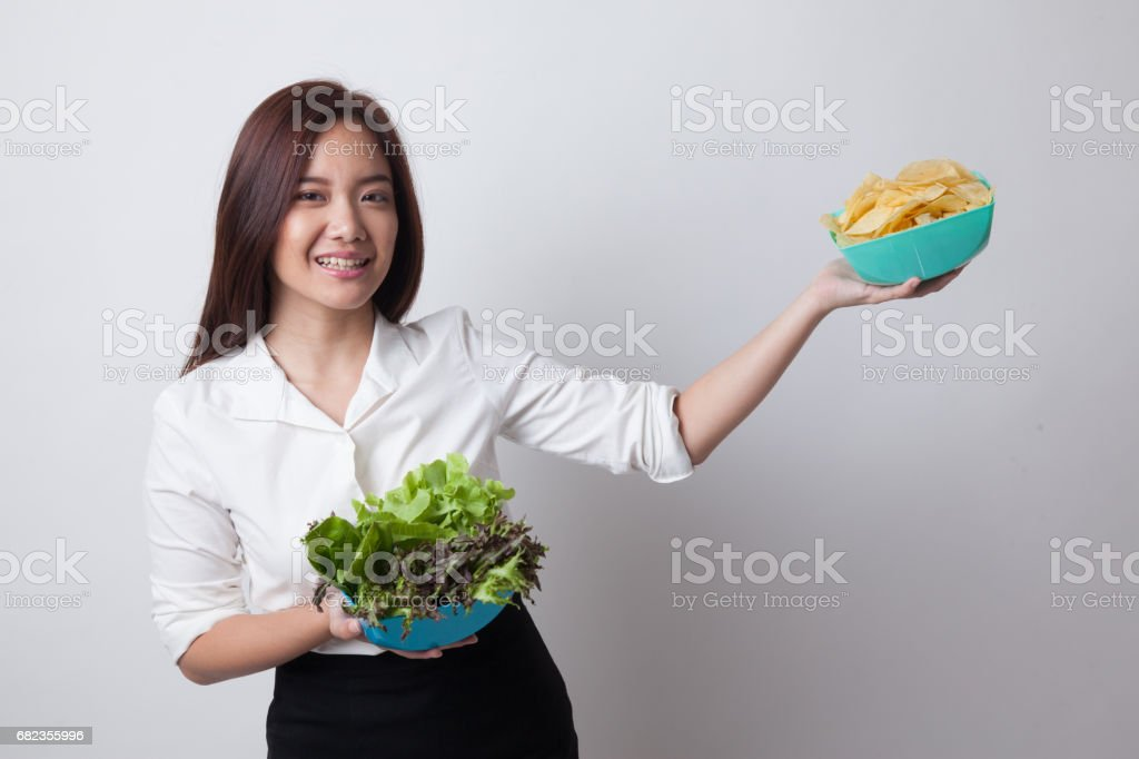 Young Asian woman with potato chips and salad. foto stock royalty-free